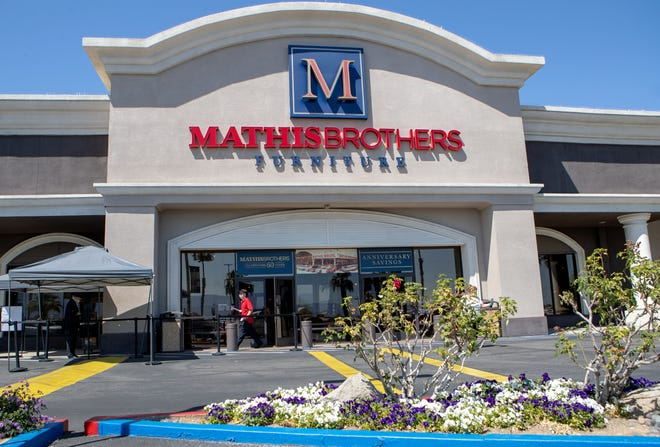 Shoppers are required to have their temperature checked before entering Mathis Brothers Furniture in Indio, Calif., on Tuesday, April 14, 2020.