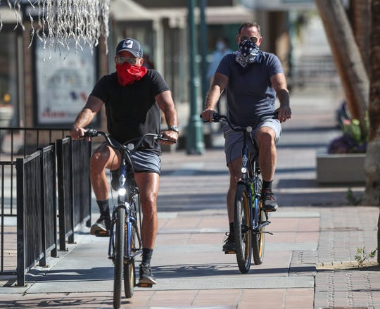 People ride their bikes with their faces covered through in downtown Palm Springs, April 13, 2020.