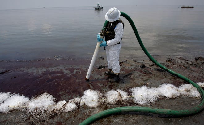 A worker uses a suction hose to remove oil washed ashore from the Deepwater Horizon spill June 9, 2010, on Grand Terre Island, just east of Grand Isle.