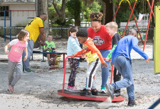 Volunteer Charese Williams, center, spins children on the playground at the House of Prayer Learning Center in Pensacola on Tuesday. The center is serving children of health care workers and first responders that must work during the coronavirus pandemic.
