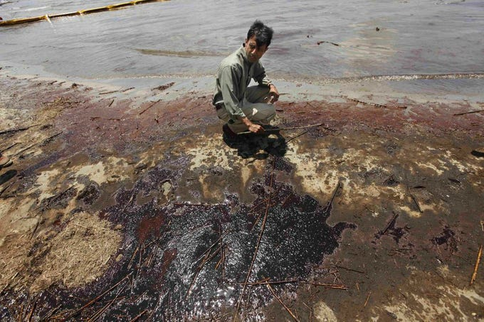 Louisiana Gov. Bobby Jindal looks at oil that got past booms as he tours a land bridge in 2010 built to hold back oil from the Deepwater Horizon oil spill. AP file photo