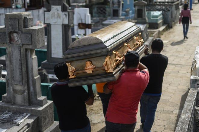 Cuatro hombres cargan sobre su hombro a su familiar fallecido, en un cementerio en Coatzacoalcos, Veracruz, México. Foto archivo.