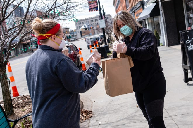 Kate's Downtown employee Nicole Jacobs, right, hands  Jeanne Palmateer her takeout order Tuesday, April 14, 2020, in downtown Port Huron. Guests aren't allowed inside Kate's during the coronavirus pandemic, but the restaurant is doing curbside pickup for takeout orders.