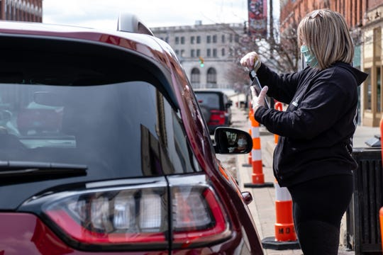 Kate's Downtown employee Nicole Jacobs, right, helps a guest check-out on a tablet that's been disinfected Tuesday, April 14, 2020, in downtown Port Huron. Guests aren't allowed inside Kate's during the coronavirus pandemic, but the restaurant is doing curbside pickup for takeout orders.