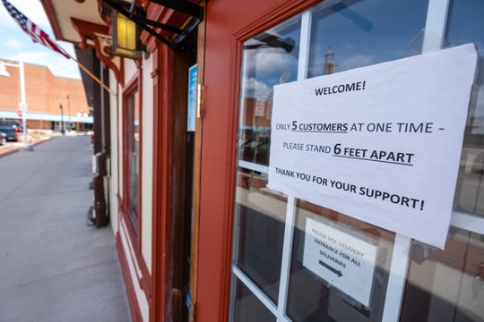 A sign on the door of Chef Shell's asks customers to respect social distancing while also limiting the number of people in the restaurant.