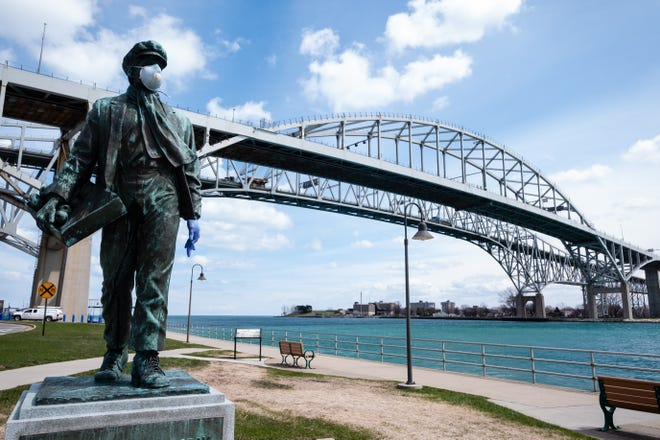 The Thomas Edison statue is decorated in personal protective equipment as it stands near the Blue Water Bridge Tuesday, April 14, 2020, in Port Huron.