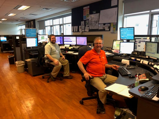 (from left) Communications officers Dave Ponke and Dan Favre answer calls at the St. Clair County Central Dispatch center.