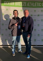 John Jay distance runner Patrick Cullen poses with his coach, Charles Sommerlad, before competing in the track and field championships in March.