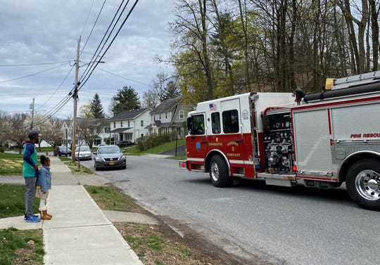 Todd Morris and daughter Skylar stand along Marian Avenue in the City of Poughkeepsie as two fire trucks pass by with a sign wishing Skylar a happy birthday.