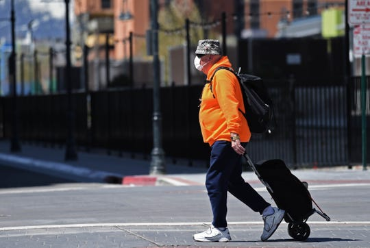 A man wearing a respirator mask walks along Virginia street in downtown Reno, Nevada on Monday April 13, 2020.