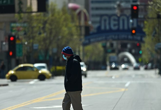A man wearing a respirator mask crossed the street in downtown Reno, Nevada on Monday April 13, 2020.