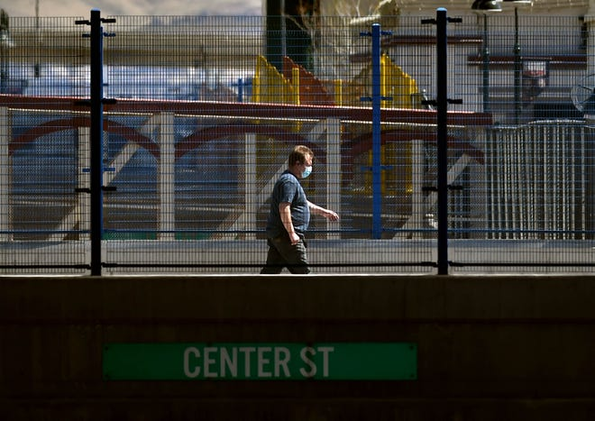 A man wearing a respirator mask walks along North Center Street amid the coronavirus pandemic in downtown Reno, Nev., on Monday, April 13, 2020.