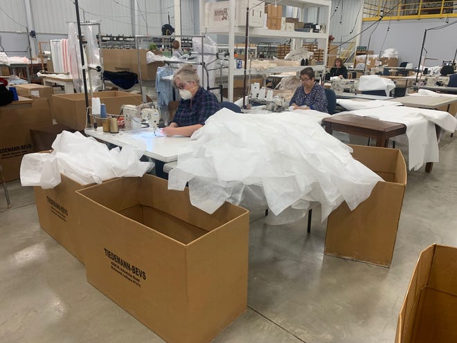Employees at Tiedemann-Bevs Industries in Richmond work to produce isolation gowns for health care employees and first responders.
