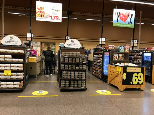 Tape marks show social distancing inside Wegmans on Mt. Read Blvd. in Greece, Tuesday, April 14, 2020.  Some employees chose to wear masks while others did not.