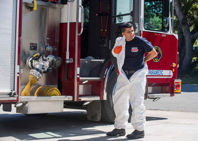Regional Fire Captain Larry Freitas puts on the personal protective equipment (PPE) outside the Monterey County Regional Fire District Toro Station 1 on Friday, April 14, 2020.