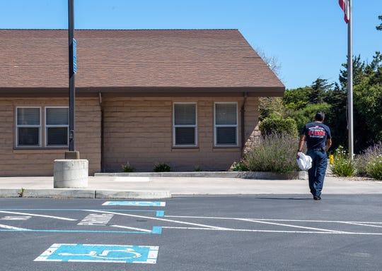Capitán de Bomberos Larry Freitas camina hacia la Monterey County Regional Fire District Toro Station 1 despues de mostrar el uso de equipo de protección personal (EPP) frente al coronavirus el viernes, 14 de abril 2020.