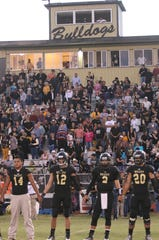 The Brady High School football team stands on the sideline before Friday's homecoming game against Clyde at Bulldog Stadium on Oct. 3, 2014.