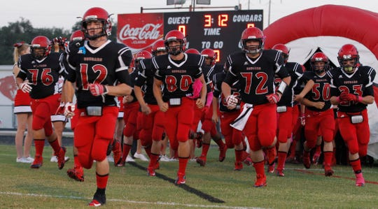 The Christoval High School football team charges onto the field before a 2013 game against Eldorado.