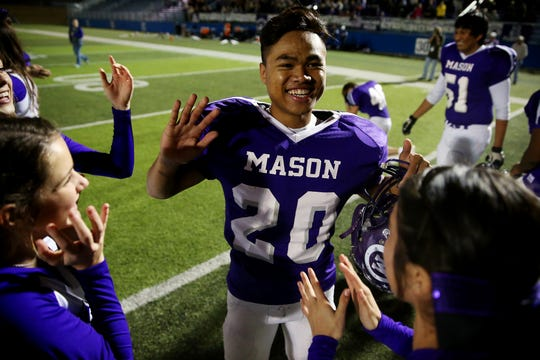 Mason High School's Go Chanriang celebrates with teammates and cheerleaders after a 27-7 win over Centerville in the state semifinals on Dec. 12, 2014.