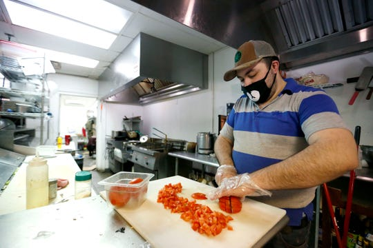 Sean Matar chops tomatoes at Riad on Tuesday, April 14, 2020. Matar's dad, Riad Matar, owns the restaurant and they both plan to use their stimulus checks to pay restaurant bills.
