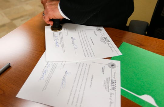 Greene County Clerk Shane Schoeller stamps the Greene County Seal into a signed document with the oath of office after a swearing in ceremony for Springfield Public School board members at a board meeting on Tuesday, April 14, 2020.
