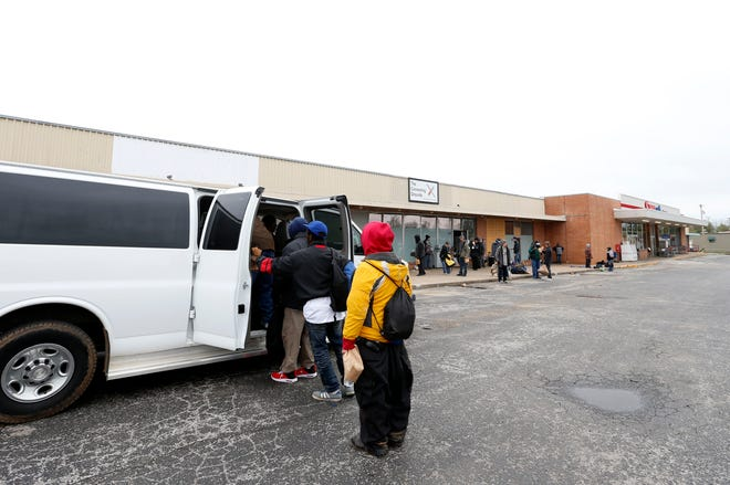 Homeless people load into a van at The Connecting Grounds on Commercial Street to go to emergency cold weather shelters on Monday, April 13, 2020.