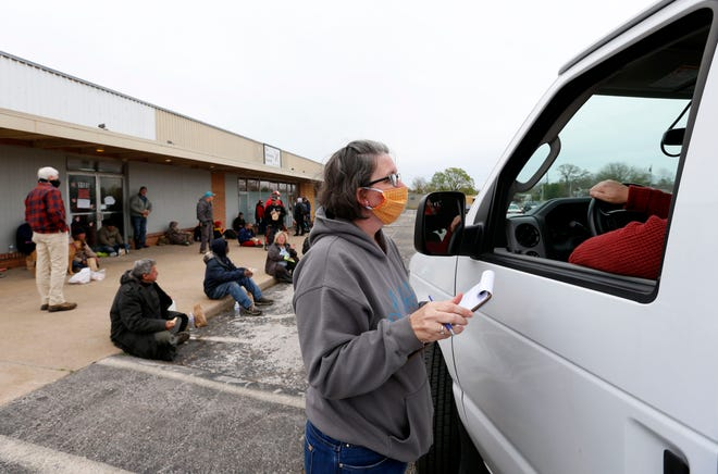 Pastor Christie Love talks with a driver transporting homeless people to emergency cold weather shelters outside the Connecting Grounds on Monday.