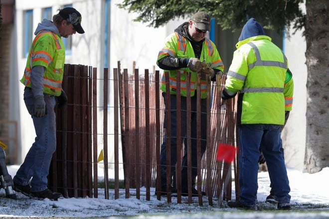 Portage County municipal workers erect temporary fencing on Tuesday, April 14, 2020, at the Portage County Health Care Center in Stevens Point, Wis. The fencing is being put in place to prevent visitors, who have been visiting residents from outside of their windows, from potentially violating social distancing guidelines.Tork Mason/USA TODAY NETWORK-Wisconsin