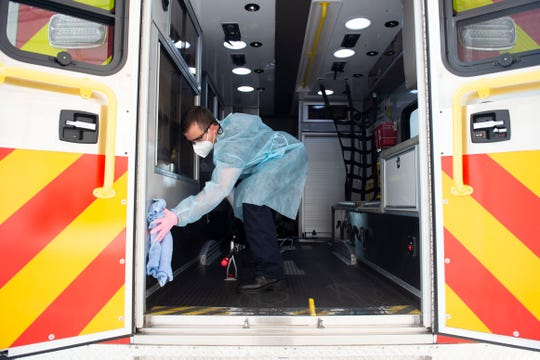 Following the delivery of a patient to the Cleveland Clinic Martin North Hospital emergency room, Martin County Fire Rescue Firefighter/EMT Tony Pellegrino cleans the Rescue 18 ambulance with Oxivir spray, part of a new process to sanitize rescue vehicles during the coronavirus pandemic Tuesday, April 14, 2020, at the hospital in Stuart. Each time a patient is transported, firefighters wear personal protective equipment as they spray down the bed, spray down the truck and cab, then use an electrostatic backpack sprayer to further disinfect the truck.