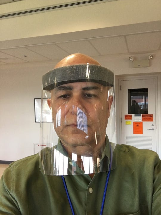 Tariq Rahman, principal research engineer at Nemours, models the disposable face shields using a foamy headband created at the hospital.