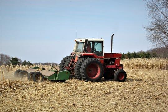 Jeff Schumacher chops cornstalks from last fall's corn harvest on his farm in Fall Creek on a warm April day.