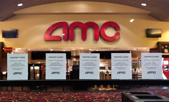 """""""Theater closed"""" signs are posted in front of AMC movie theaters on March 17, 2020, in Montebello, California, as the chain closed down for six to 12 weeks due to coronavirus."""