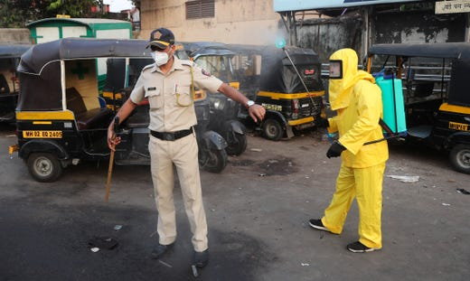 A civic worker sprays disinfectant on a policeman standing guard after a protest by migrant workers against the extension of the lockdown, in a slum in Mumbai, India, April 14, 2020. Indian Prime Minister Narendra Modi on Tuesday extended the world's largest coronavirus lockdown to head off the epidemic's peak, with officials racing to make up for lost time.