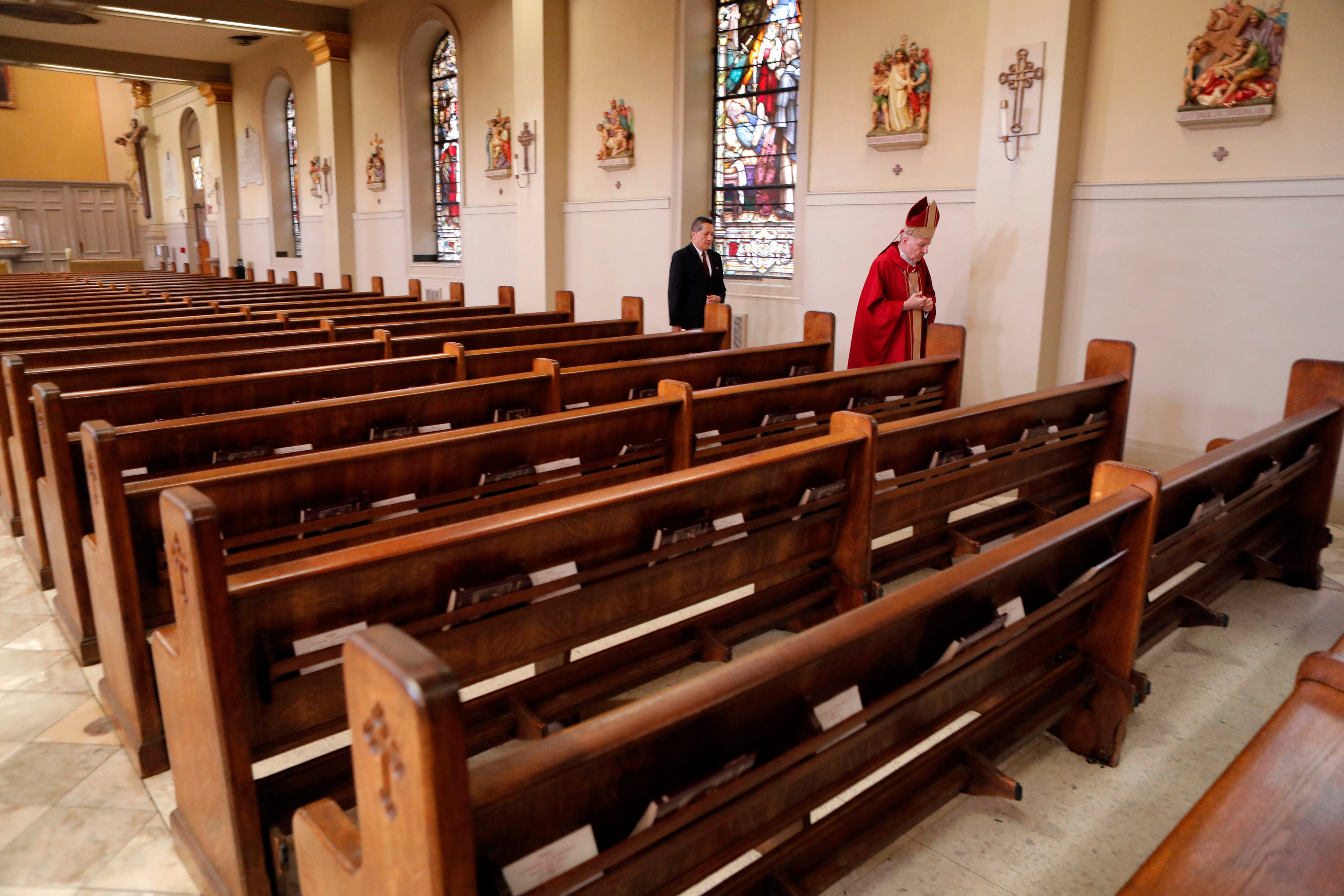 Archbishop Gregory Aymond walks through St. Louis Cathedral, without any congregants, to celebrate Good Friday services in in New Orleans, Friday, April 10, 2020. The service was live streamed due to the new coronavirus pandemic.