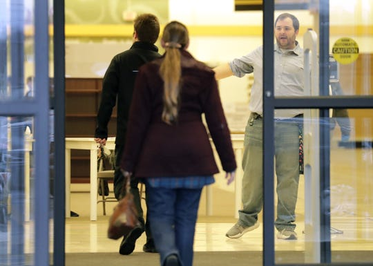 Neenah Deputy City Attorney Adam VandenHeuvel directs residents as they enter the former Shopko store on Election Day. The building served as the city's sole polling place.