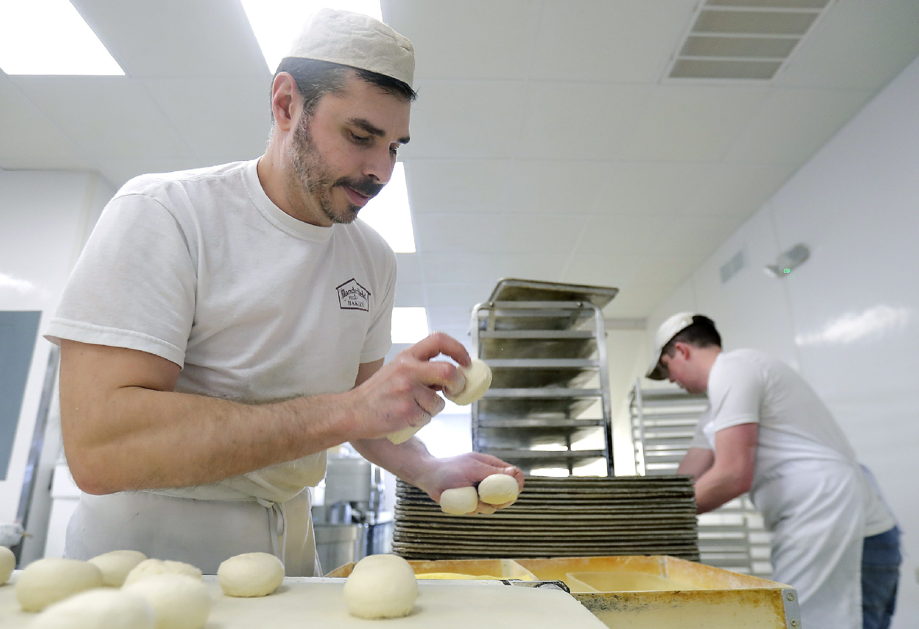 At Manderfield's Home Bakery on Appleton's east side, Bradley Jarvais, left, and JT Heenan roll dough for buns for wholesale accounts. The bakery will reopen this shop Wednesday, April 22, for retail customers.