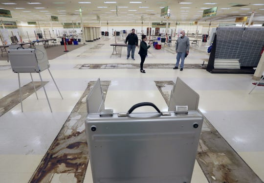 Neenah Deputy City Attorney Adam VandenHeuvel, left, Deputy City Clerk Stephanie Cheslock and Common Council President Todd Stevenson set up the former Shopko store as a polling place. The store might be used again for future elections if available.