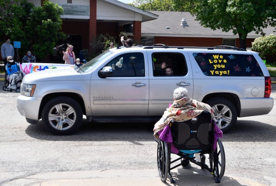 A boy waves during a parade for residents at Wisteria Place Nursing and Rehabilitation on April 14. Visitation has been limited greatly during the coronavirus pandemic.