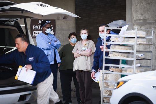 United Food & Commercial Workers (UFCW) Local One representatives help deliver trays of food to St. Elizabeth employees on Tuesday, April 14, 2020 in Utica.