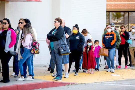 Customers wait in line to enter Ollie's Bargain Outlet on Wednesday, April 15, 2020. The discount retailer is allowing 50 people at a time into its stores. Wednesday was its grand opening in Corpus Christi.