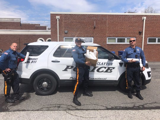 Members of the Clayton Police Department show off a recent donation of food from the Tri-County Conference's Athletes in Action program.