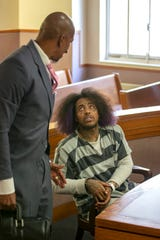 Attorney Clyde Bennett, II, talks with his client Rashaan Davis, 26,  at the Hamilton County Courthouse on Wednesday, April 15, 2020. Judge Alan Triggs dropped charges that alleged Davis violated Ohio's stay-at-home order by recording a large gathering in Over-the-Rhine. An inciting violence charge remains pending until a grand jury can be convened, likely in May. Grand jury proceedings have temporarily been suspended for safety reasons during the pandemic. In the meantime, Judge Alan Triggs released Davis from jail on home arrest.