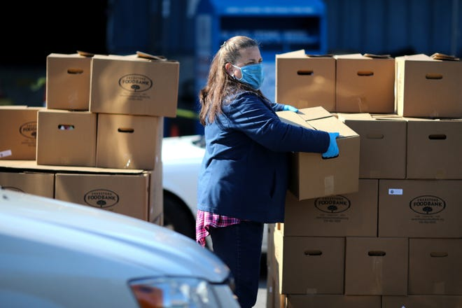 Volunteers and staff from St. Vincent de Paul and the Freestore Foodbank distribute more than 600 boxes of food, Wednesday, April 15, 2020, in Erlanger, Ky.