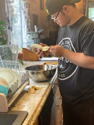 Jason Neighbor learns to make banana bread from his direct support professional. Some work is being done online, but providers are still going into homes to work with clients of the Coshocton County Board of Developmental Disabilities during the COVID-19 pandemic.