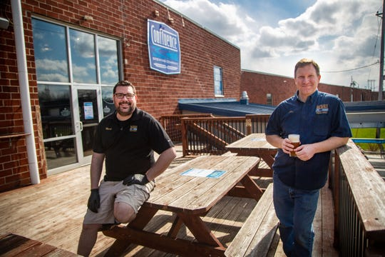 Confluence taproom manager Mark David and president John Martin stand outside of Confluence Brewing Tuesday on a deck that would normally be full of customers. With the taproom and patio closed due to the governor's Covid-19 orders, Confluence is offering beer pickup in the parking lot.