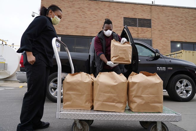 YumVillage owner and chef Godwin Ihentuge loads a cart of food while dropping off food for workers at Beaumont Hospital, Wayne on  April 13, 2020, as part of the Rescue Detroit Restaurants / Feed Health Care Heroes program.