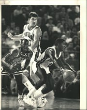 Pistons' Joe Dumars dribbles around Bulls' Michael Jordan and teammate Bill Laimbeer.