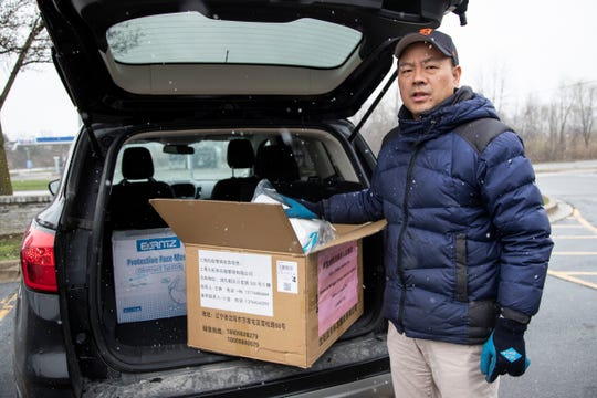 Joe Miao, one of the organizers of the Michigan Chinese American Coalition, stands with the face masks and hospital gowns that he's donating on April 15, 2020.