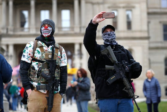 People with rifles watch outside the State Capitol in Lansing on  April 15 to protest  Gov. Gretchen Whitmer's orders to keep people at home and businesses locked during the COVID-19 outbreak.