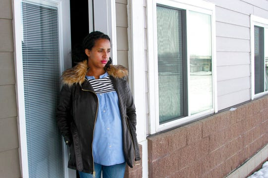 In this April 13, 2020, photo, Kulule Amosa steps out of the apartment she shares with her husband who works at the Smithfield Foods pork processing plant in Sioux Falls, S.D. He tested positive for the coronavirus this week after an outbreak at the plant.
